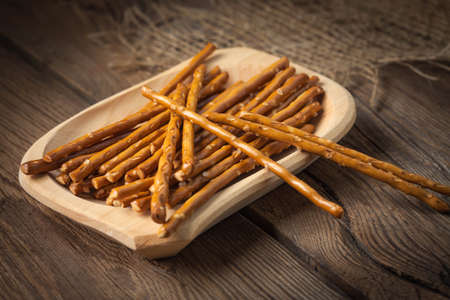 salty: Salty pretzel sticks on a dark wooden table. Stock Photo
