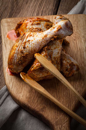 Marinated chicken drumsticks on a wooden chopping board. Dark light. Selective focus.