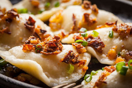 Dumplings with meat, onions and bacon on a cast iron skillet. Selective focus. Imagens