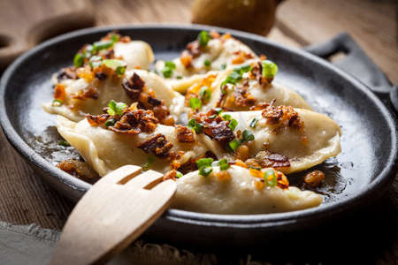 Dumplings with meat, onions and bacon on a cast iron skillet. Selective focus. Stock Photo