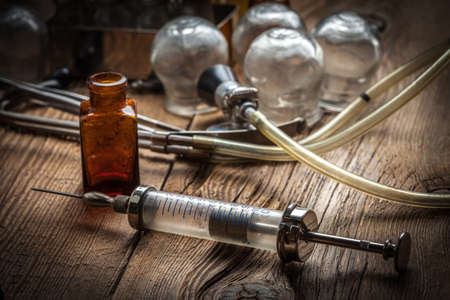 cupping glass cupping: Retro syringe, stethoscope and medical cupping glass on a wooden table. Shallow depth of field.