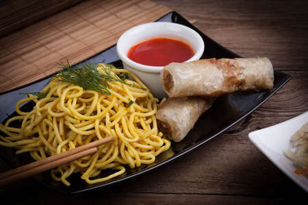Tasty Chinese spring rolls with yellow noodles. Selective focus.