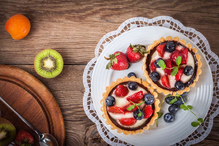Fresh homemade fruit tart with strawberries and blueberries. Selective focus. Top view.