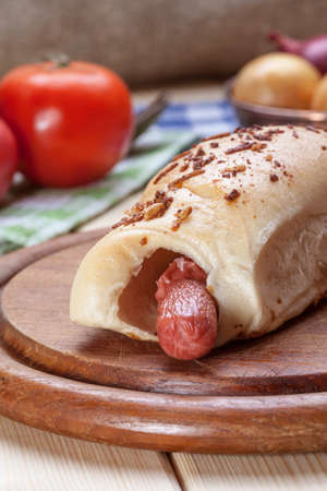 Sausage baked in dough on a wooden chopping board.