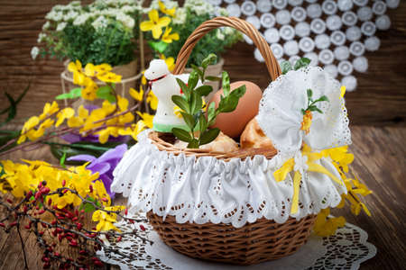 Traditional Easter basket with food on the wooden table.
