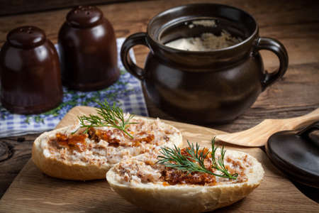 greaves: Hearty lard with greaves in a rustic stoneware pot served with fresh bread on a rustic wooden table. Dark light.