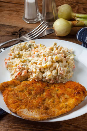 Fried pork chop in breadcrumbs, served with vegetable salad. Traditional Polish dish. Stock Photo