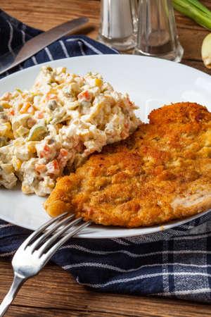 パン粉、揚げポーク チョップは、野菜サラダが付きます。伝統的なポーランド料理。 写真素材