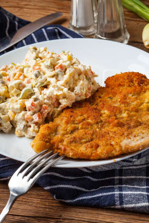 Fried pork chop in breadcrumbs, served with vegetable salad. Traditional Polish dish. Imagens