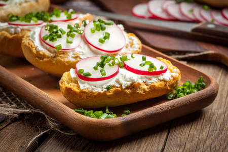 Toasts with radish, chives and cottage cheese on a wooden table. Tasty snack. Selective focus.
