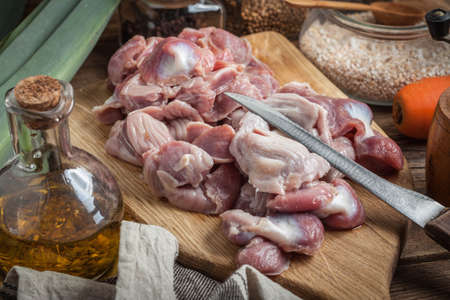 giblets cooked: Raw chicken gizzards on cutting board. Selective focus. Stock Photo