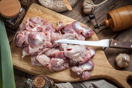 Raw chicken gizzards on cutting board. Selective focus. Imagens