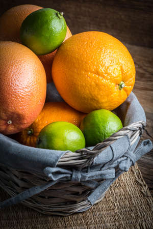 Fresh juicy citrus fruits in a basket on a wooden background.