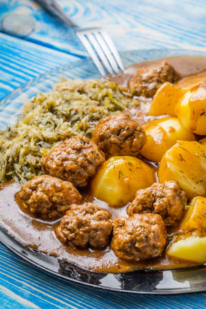 Homemade fried meatballs served with potatoes and cabbage on  plate.