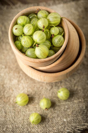 Fresh gooseberry in a wooden bowl. Small depth of field.
