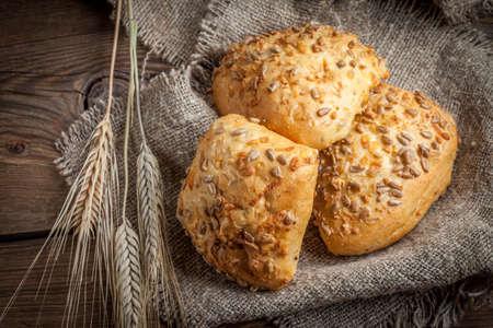 Fresh buns with sunflower seeds on jute material. Dark light.