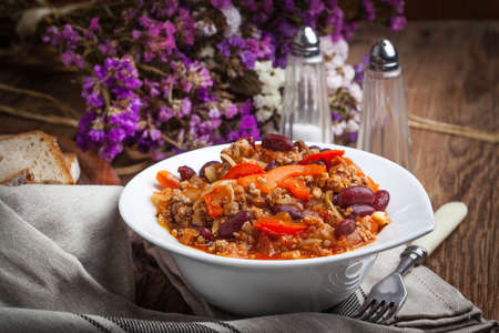 Chilli con carne with paprika, tomatoes, onion, red bean and garlic in a bowl.