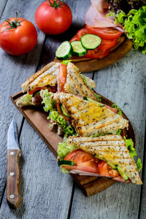 Panini sandwich with ham, tomato and lettuce  on a cutting board.