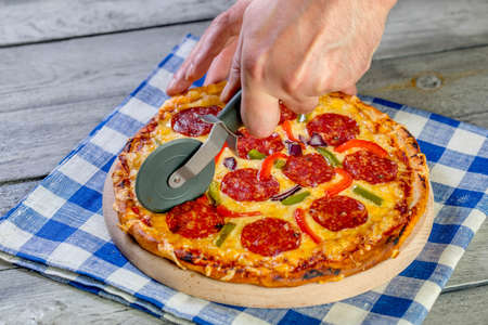 pizza cutter: Cutting pepperoni pizza on sliced with special knife.