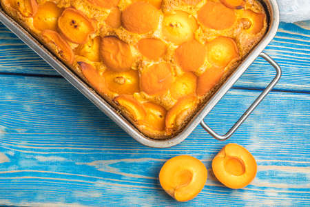 Tart with apricots on wooden table background. Top view.