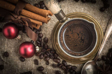 Turkish coffee in copper coffee pot on wooden background. Stock Photo
