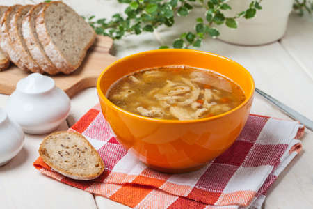 Traditional polish tripe soup with vegetables in orange bowl. Stock Photo