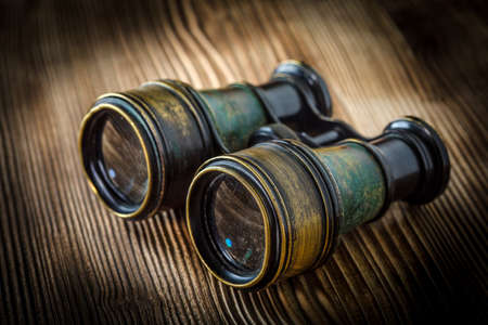 Old binoculars covered with patina on wooden background. Stock Photo