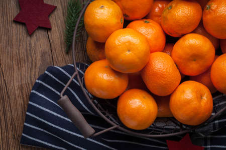 Basket of tangerines on a wooden table. Selective focus.