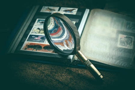 Book with postage stamps and a magnifying glass. Vintage style. Imagens