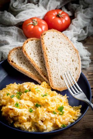 Scrambled eggs with onion and chives served with bread on a blue plate.