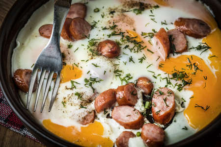 Tasty cooked egg with chopped sausages in pan.