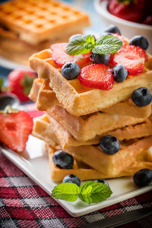 Stack of waffles with fruit on a plate. Small depth of field. Standard-Bild