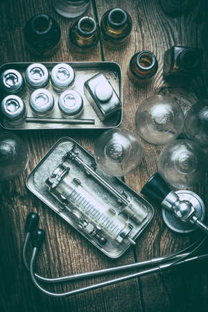 Retro syringe, stethoscope and medical cupping glass on a wooden table. Shallow depth of field. Filtered style.