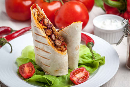 Burritos wraps with meat, beans and vegetables on wood board. Shallow depth of field.