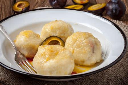 Sweet plum dumplings in metal bowl on wooden table.