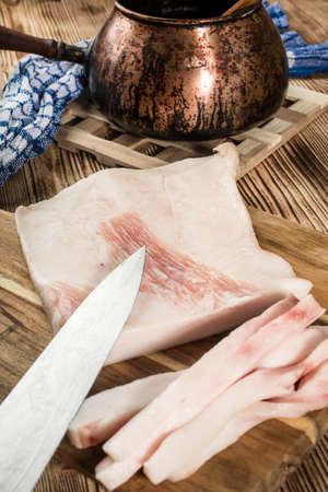 Sliced fresh lard on a chopping board.