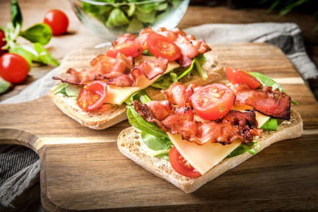 Ciabatta sandwich with arugula salad, bacon and yellow cheese on wooden board.
