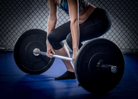 Woman workout in fitness gym with barbells.