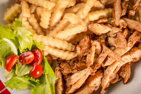 Greek gyros with fries and salad on plate.