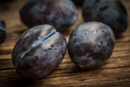 Garden plums on wooden table.  Stock fotó