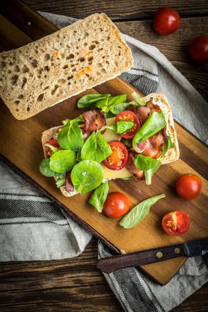 Ciabatta sandwich with arugula salad, bacon and yellow cheese on wooden board. Top view.