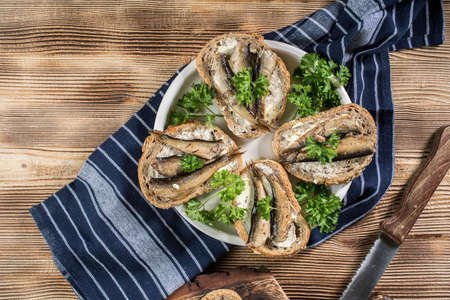 Sandwich with sprats on wooden table. Top view. Reklamní fotografie
