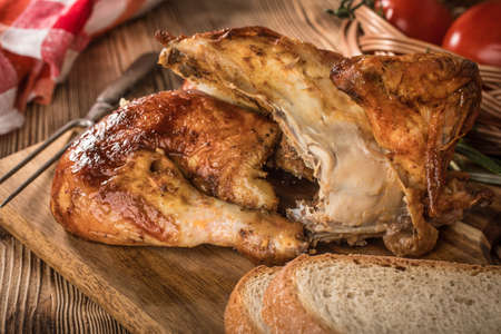 Pieces of roasted chicken on a wooden chopping board.