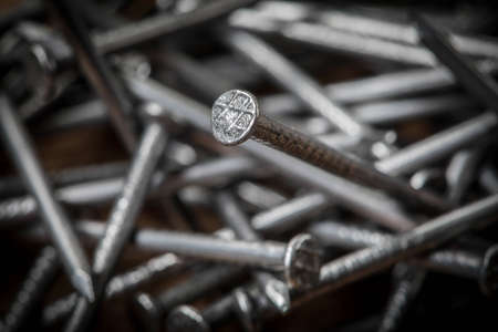 Steel nails on wooden background. Selective focus. Stockfoto