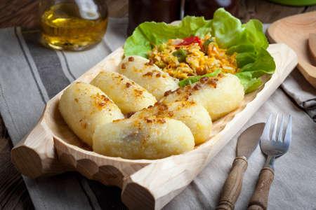 Potato dumplings stuffed with minced meat on wooden table.