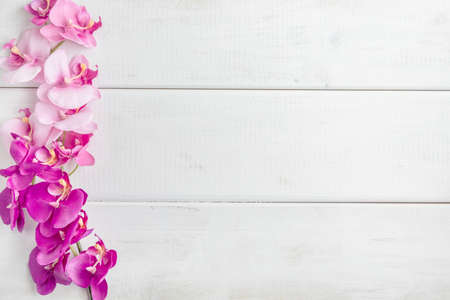 Artificial orchids on white wooden background. Top view. Copy space.