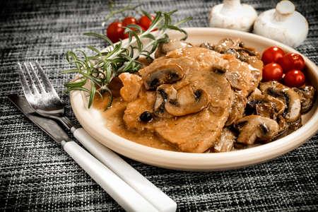Stewed pork chop in a bright mushroom sauce.