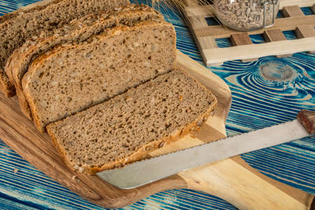 Sliced traditional wholemeal bread on a wooden board with bread knife.