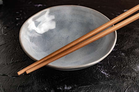 Bowl with chopsticks to eat on a black background.