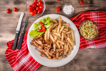 Greek gyros with fries and salad on plate. Top view. Stock Photo